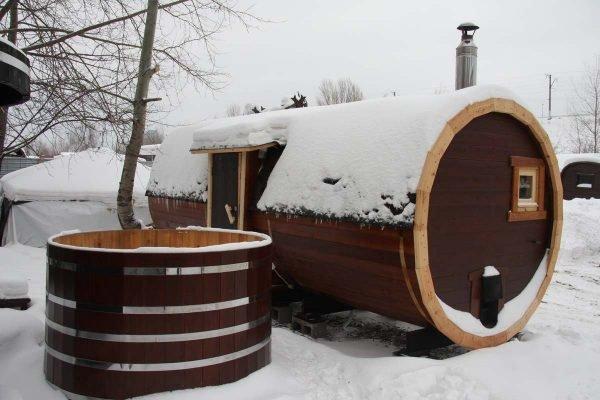 Баня-бочка из тёмного дерева зимой