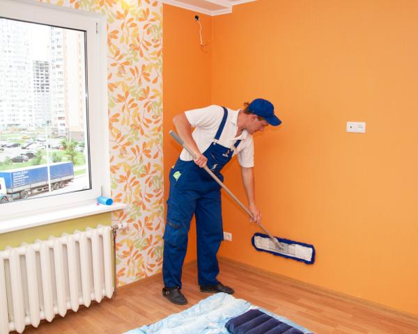 Мужчина моет стену, покрашенную масляной краской, с помощью швабры