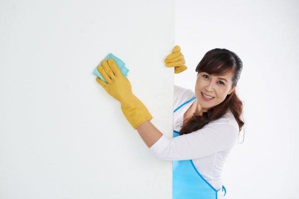 Женщина моет стену тряпкой