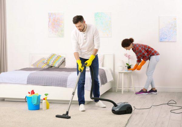 Семейная пара делает уборку в квартире